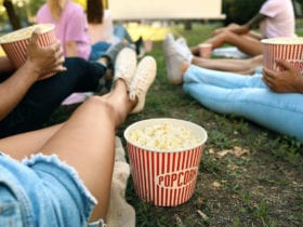 Outdoor movie screens: Young people with popcorn watching movie in open air cinema. (Photo: Shutterstock)