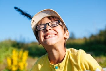 boy wearing glasses and a hat smiling in the sun