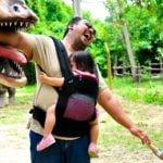 parent with young child and baby joking with dinosaur statue