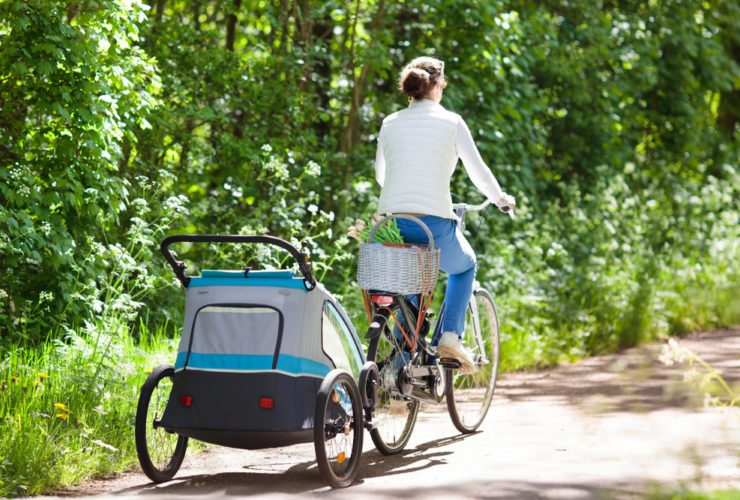 Young mother riding bicycle with baby bike trailer in sunny summer park. (Photo: Shutterstock)