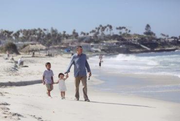 multigenerational family travel - grandparent with grandkids on beach