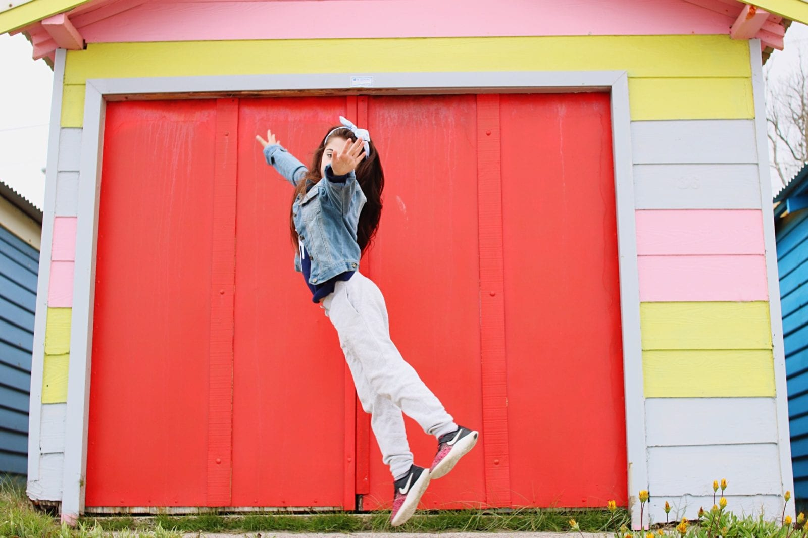 girl in sneakers jumping in front of colorful house