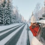 Teen girl in car over snowy forest on winter road trip.