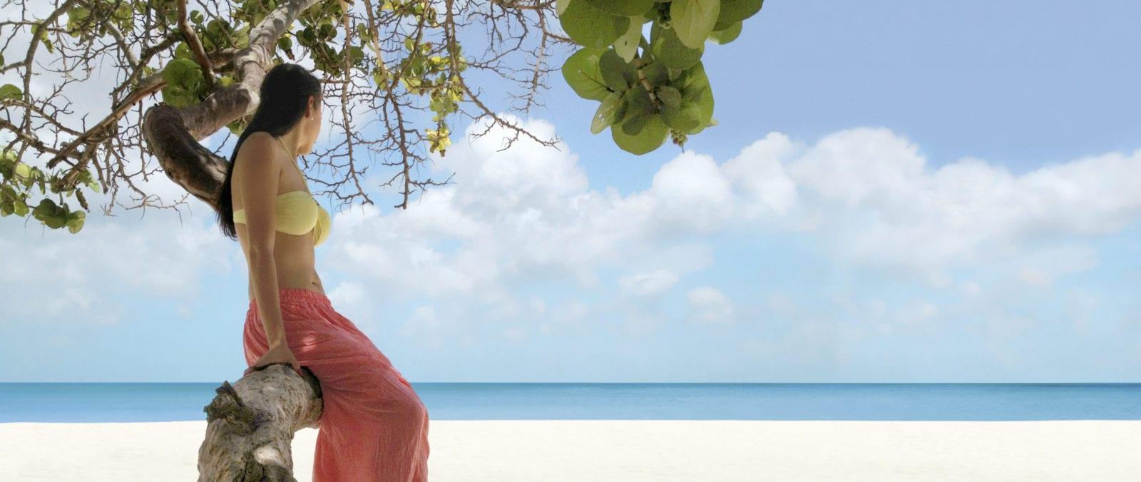 Woman in Palm Tree on Manchebo Beach (Photo: Manchebo Beach Resort & Spa)