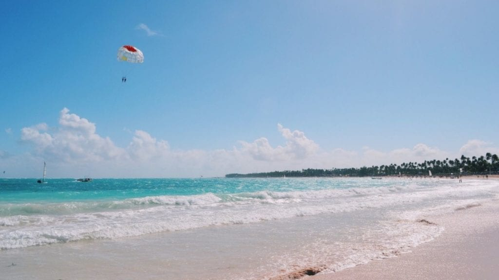 Punta Cana beach with waves and parasailers in background