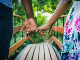 couple holding hands while walking over a bridge: best vacation spots for couples