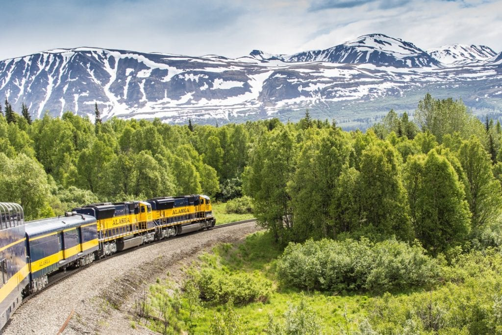 Alaska Railroad train with mountains in background of scenic train trip