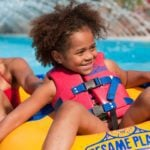 Child and parent floating down Rambling River at Sesame Place, an amusement park for young kids