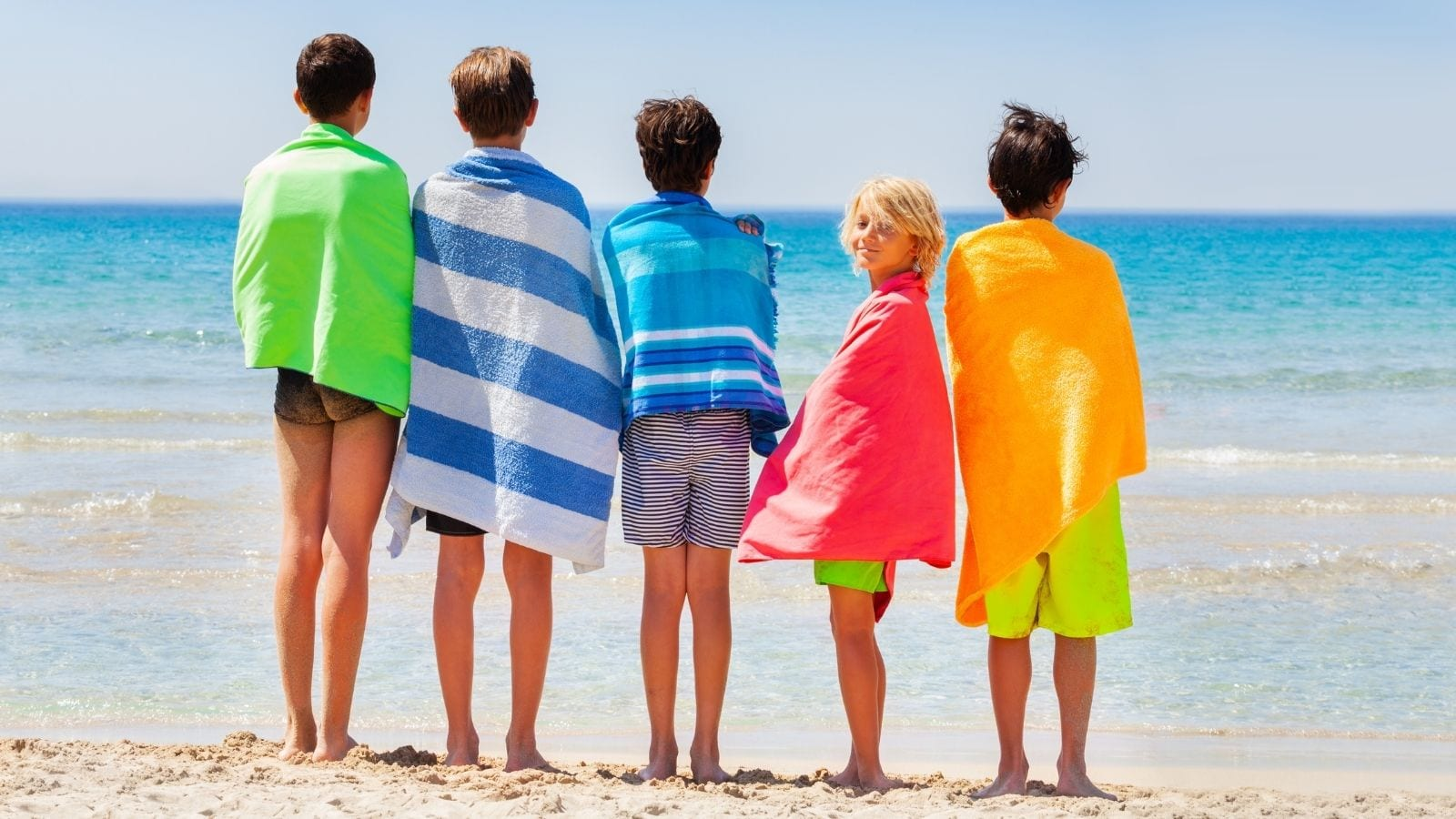 Kids drying off with beach towels after swimming (Photo: Sergey Novikov / Shutterstock)