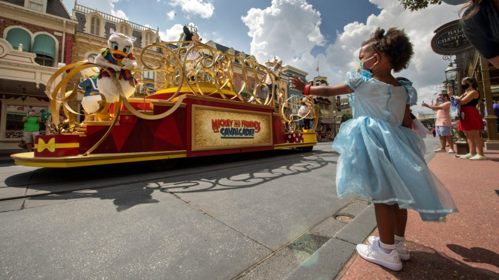 Toddler wearing a dress watching the parade at Walt Disney World's Magic Kingdom, an amusement park for kids that caters to toddlers