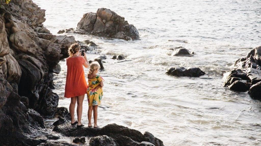 Mother and daughter climbing rocks on the beach in Maui, Hawaii (Photo: @debb_alba via Twenty20)