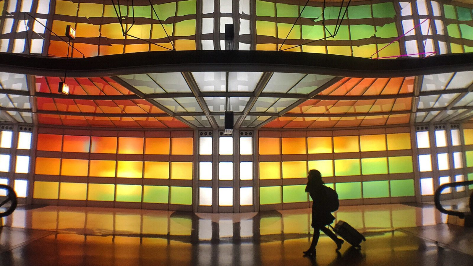 person rolling luggage in front of stained glass display in airport terminal
