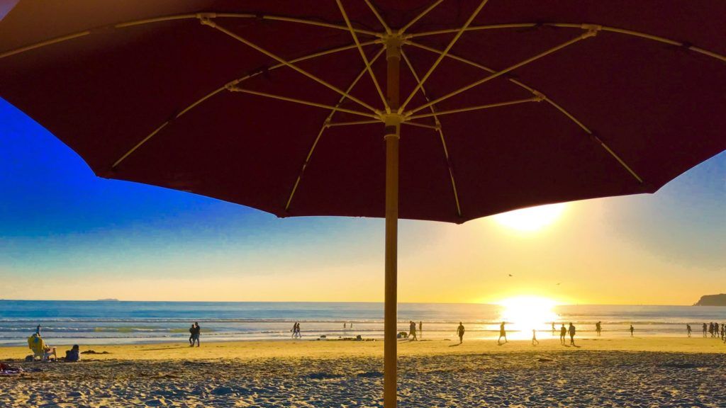 View of beach and water at sunset from under a beach umbrella in Coronado, California, a skip-gen vacation destination