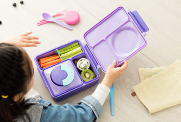 child looking into OmieBox bento box with food items inside