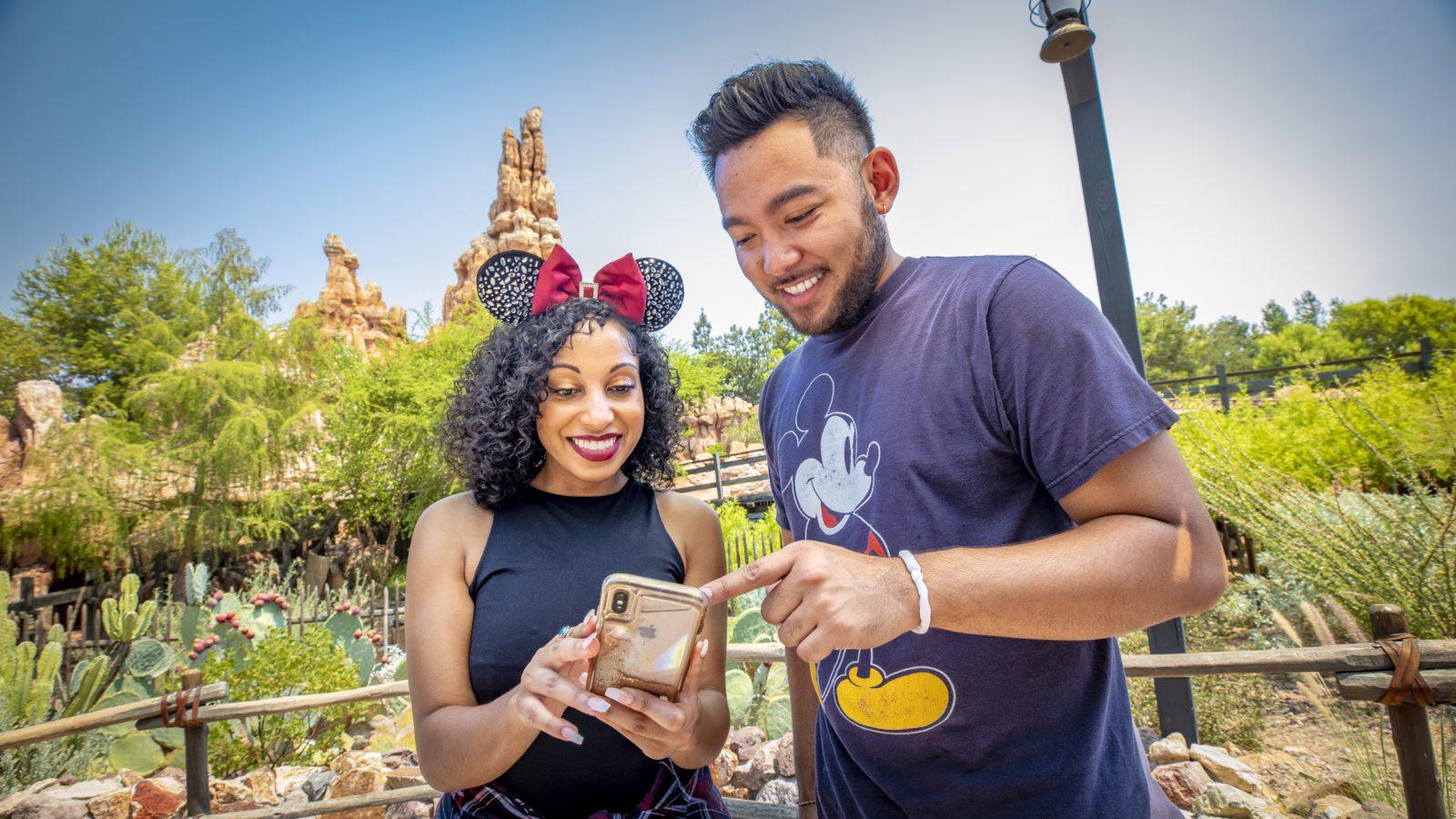 Two people at Disneyland looking at their phones